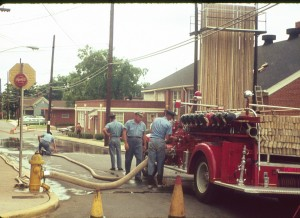 Four firefighters inspecting fire hose on American LaFrance fire engine