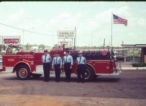 Four firefighters standing with an American LaFrance Fire Truck