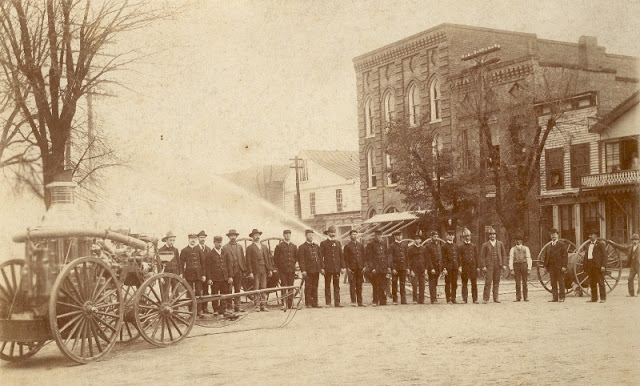 Monroe Fire Department in 1900s with horse drawn Silsby Steamer engine in downtown Monroe